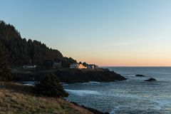 Houses on the edge of a cliff at sunset in a cove of the Pacific Ocean on the coast of Oregon, USA. stock photo