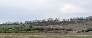 House and a scorched field on a hillside. Houses in a field on a hillside. The photo clearly shows how the dry grass was scraped out of absurd prejudices about royalty free stock photography
