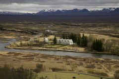 Houses in the fields. This picture is showing a group of a few houses in the middle of a field in Iceland. There are high mountains in the background, a small Stock Image