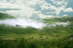 Houses in the fog on the mountainside. Tourist houses on a hill in the forest. stock image