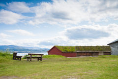 Houses with grass covered roofs and benches near a fjord Royalty Free Stock Photo
