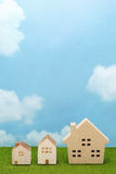 Houses on green grass over blue sky and clouds. Royalty Free Stock Photo