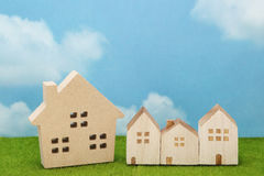 Houses on green grass over blue sky and clouds. Royalty Free Stock Images