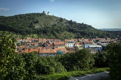 Houses of a historic city with red roofs under a forested hill Royalty Free Stock Images