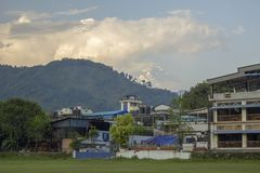 Houses hotels against a green hill and the snowy top of Mount Annapurna in the clouds. A houses hotels against a green hill and the snowy top of Mount Annapurna royalty free stock images