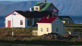 Houses with Icelandic flags on the Atlantic coast. Andreev. Houses with Icelandic flags on the Atlantic coast. People are in the yard of the house. Strong wind stock footage