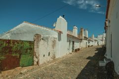 Houses with iron garage gate on street of Evoramonte. Humble white wall houses with iron garage gate in a sunny day, on the cobblestone main street of Evoramonte royalty free stock image