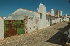 Houses with iron garage gate on street of Evoramonte. Humble white wall houses with iron garage gate in a sunny day, on the cobblestone main street of Evoramonte stock photography