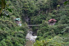 Houses in the jungle of Baños, Ecuador. Two houses and a small waterfall in the middle of them in the jungle of the town of Baños, Ecuador stock images