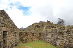 Houses of Machu Picchu under cloudy blue sky Royalty Free Stock Photo
