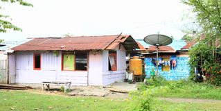 Houses with satellite antenna in Manokwari. Houses made from wooden planks with roof from corrugated iron with satellite antenna, water reservoir and drying royalty free stock photos