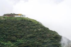 Houses on a mountain in the clouds Stock Photos