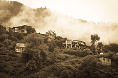 Houses in mountains covered by clouds and rain Royalty Free Stock Photo