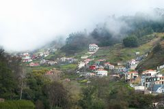 Houses in the mountains in the midst of a forest and thick fog. Settlement in the mountains among the forest and dense fog on the island of Madeira Stock Images