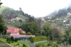 Houses in the mountains in the midst of a forest and thick fog. Settlement in the mountains among the forest and dense fog on the island of Madeira Royalty Free Stock Image