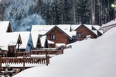 Houses in the mountains. Wooden, snow-covered houses in the mountains, winter, smoke comes from the chimneys, pine forest on the background Royalty Free Stock Image