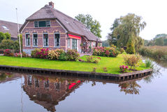 Houses near a canal. Of Giethoorn in Holland on a sunny day. You can see some trees royalty free stock photo