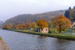 Houses near the river in the wood an autumn landscape Stock Image