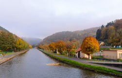 Houses near the river in the wood an autumn landscape Royalty Free Stock Photo
