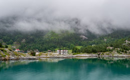 Houses of norwegian village at fjord's shores . Stock Photo