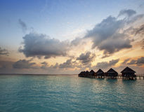 Houses over the sea at sunrise. Maldives Royalty Free Stock Image