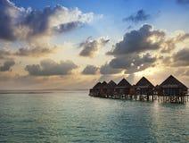 Houses over the sea at sunrise. Maldives Stock Photos