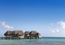 Houses over the transparent quiet sea water. Tahiti Stock Photo