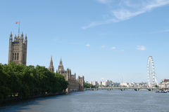 Houses of Parliament and London Eye on the Thames. London's Contrasting Skyline with the Historic Houses of Parliament and the Modern Millennium Wheel Seen from Royalty Free Stock Photos