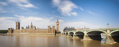 Houses Of Parliament Long Exposure. Long exposure panorama of the Houses of Parliament in London with blue sky and the Westminster Bridge to the right stock photography