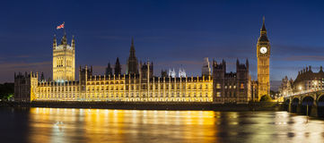 Houses Of Parliament At Night Panorama. Panoramic long exposure night shot of the Houses of Parliament in London with blue sky and the Westminster Bridge in the Royalty Free Stock Photos