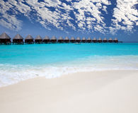 Houses on piles on sea against the sky with white clouds. Maldives. Stock Image