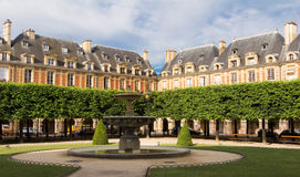 The houses of place des Vosges, Paris, France. The house fronts of place des Vosges in Paris are all built to the same design of red brick with strips of  stone Stock Images