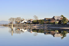 Houses reflecting on the water in Mud Bay Stock Image