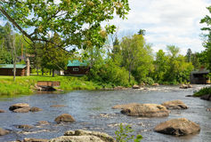 Houses by a river in northern canada. Cottages dotting the banks of a river in the summertime stock photo