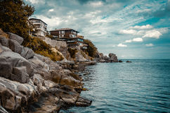 Houses on a rock cliff. On seashore Stock Photos