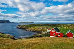 Houses on sea coast on cloudy sky in Torshavn, Denmark. Wooden houses on seascape. Beautiful landscape view. Summer. Vacation in country. Architecture and stock photography