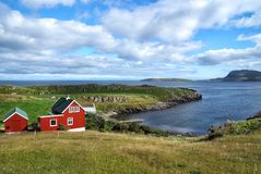 Houses on sea coast on cloudy sky in Torshavn, Denmark. Wooden houses on seascape. Beautiful landscape view. Summer. Vacation in country. Architecture and royalty free stock image