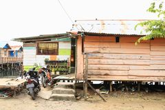 Houses by sea in Manokwari. Houses made from wooden planks with roof from corrugated iron with two parked motorbikes by the sea in Manokwari, Papua Barat stock photos