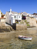 Houses on the sea shore with a boat Stock Images