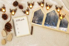 Houses shape wooden photo frames over cozy and warm fur carpet. Top view 2018 goals list with notebook. Stock Image