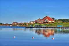 Houses on shore of blue lake. A view of beautiful houses on the shore of a lake that reflects the brilliant blue, cloudless sky on a bright, sunny day Royalty Free Stock Photos