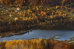 Houses on the shores of a lake in the colored woods stock photos