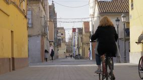 Houses and some people in Barraca street in Valencia, Spain. Valencia, Spain - January 13, 2018: Barraca street view. Some people walking and family cycling stock video