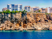 Houses stand on a cliff by the sea shore Royalty Free Stock Images