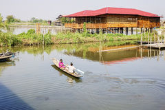 Houses on stilts on Inle Lake, Shan, Myanmar. People take a boat near house on stilts on Inle Lake, Shan, Myanmar. Fishermen in Myanmar have a conical net to Royalty Free Stock Image
