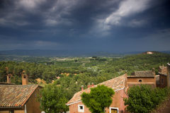 Houses and trees in Provence, with dark, stormy sky Stock Image