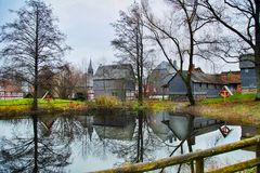 Houses and trees reflecting in pond. Houses and leafless trees on the shore reflecting in a pond Stock Photography