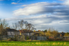Houses and trees in village in early spring. Cloudy blue sky Royalty Free Stock Image