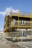 Houses under construction. A housing estate under construction with scaffolding and building material all around the site Royalty Free Stock Image