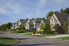 Houses on upscale suburban street in morning sunlight. Upscale houses on a suburban street in the USA Stock Photography